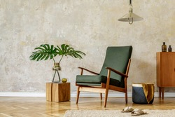 Minimalist concept of home interior with retro armchair, pendant lamp, wooden commode, tropical leaf in vase, wooden cube, carpet, basket and elegant accessories in modern home decor.