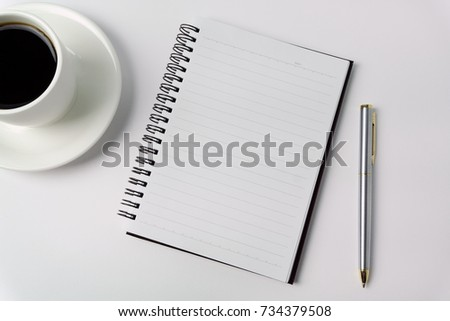 Minimalist concept - Top view of office desk wit cup of coffee, open notepad and pen on white background #734379508