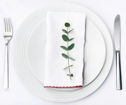 Minimalist dinner place setting, green twig on white napkin on plain crockery and silverware