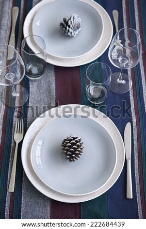 Minimalist dinner place setting with single pine cone as decoration, a simple christmas holiday