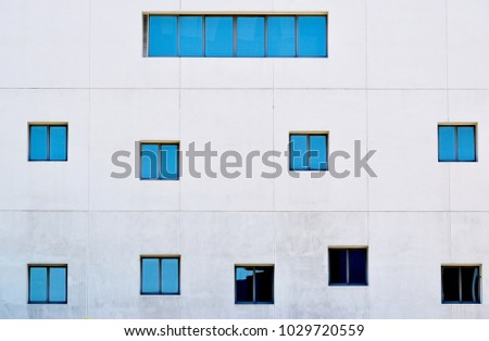 Minimalist exterior of an office building with interesting and random square windows in Singapore #1029720559
