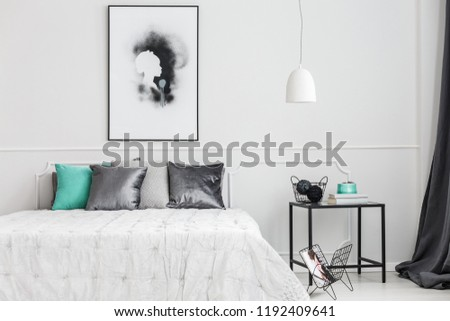 Minimalist, framed poster mock-up on a white wall of an artistic bedroom interior with elegant decor and gray textiles #1192409641