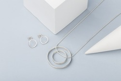 Minimalist geometric silver necklace and circle stud earrings on gray background. Modern jewelry. Product concept for jeweler