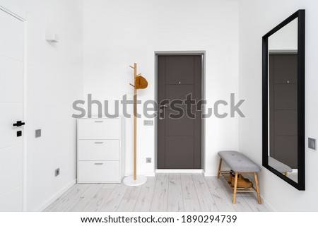 Minimalist hallway with modern interior design in contemporary apartment. Comfortable shoe storage bench near black frame mirror on white wall. Wooden coat hanger in hall with chest drawers