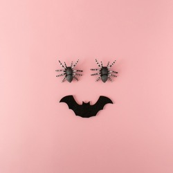 Minimalist ic happy Halloween face made of spiders and bat on pink background. Creative fun Halloween concept. Flat lay.