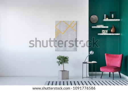 Minimalist interior in white and green with red armchair, lamp and book on the table, plant, carpet on the floor, painting on the wall and shelves #1091776586