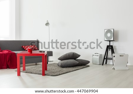 Minimalist interior of a bright living room with a grey sofa, red coffee table and a pile of cushions