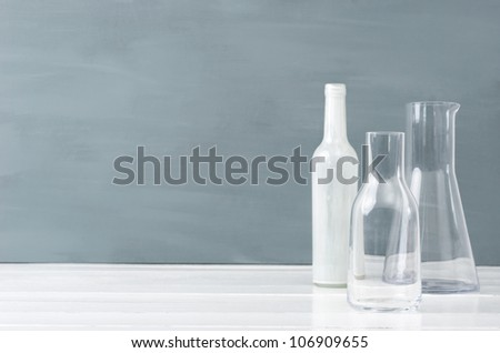 Minimalist interior simple modern elegant decorating table top with grey background, glass bottles and lots of copy space