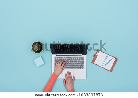 Minimalist light blue workspace with laptop, organizer and woman connecting online, top view