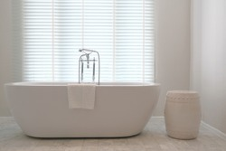 Minimalist luxury bathtub with traditional faucets in front of venetian blinds