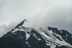 Minimalist monochrome atmospheric mountains landscape with big snowy mountain top in low clouds. Awesome minimal scenery with glacier on rocks. Blue white high mountain pinnacle with snow in clouds.