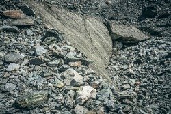 Minimalist nature background with stones on ice of glacier. Minimal natural backdrop with glacial ice among moraines. Beautiful landscape with texture of glacier ice in stone dust. Glacier surface.