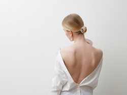 Minimalist photo , Fashionable girl in stylish summer things - white shirt . View from the back. Earrings, a ring . Street fashion , blogger style . Beauty . Minimalist Fashion clothes