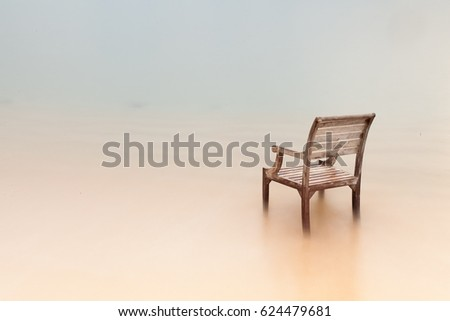 Minimalist photography. A chair at the beach, captured in long exposure. Soft focus. #624479681