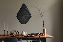 Minimalist rustic concept of dining room interior with wooden family table, design retro chairs, cup of coffee, decoration, pedant lamp and personal accessories in stylish home decor. Template.