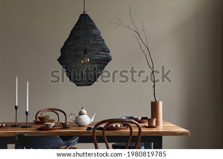 Minimalist rustic concept of dining room interior with wooden family table, design retro chairs, cup of coffee, decoration, pedant lamp and personal accessories in stylish home decor. Template. Foto stock ©