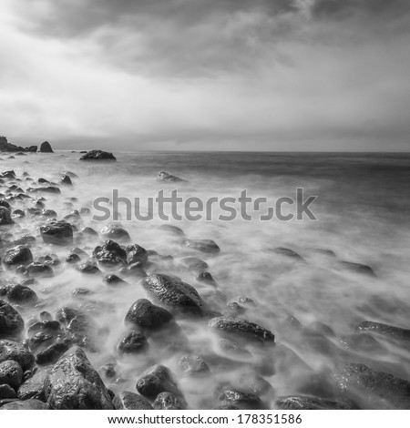 Minimalist seascape. Long exposure of sea and rocks. Black and white.