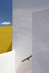 Minimalist  surreal architectural composition with white and yellow walls on the blue sky and a lonely cloud background, Spain, Andalusia, bright sunlight