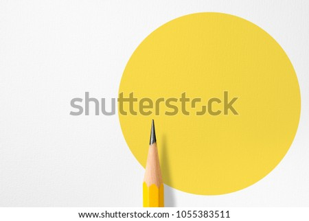 Minimalist template with copy space by top view close up macro photo of wooden yellow pencil isolated on white paper and combine with yellow circle shape. Flash light made smooth shadow from pencil. #1055383511