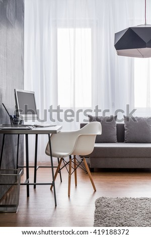 Minimalist workspace with grey desk and white designer chair arranged as a part of a very bright living room