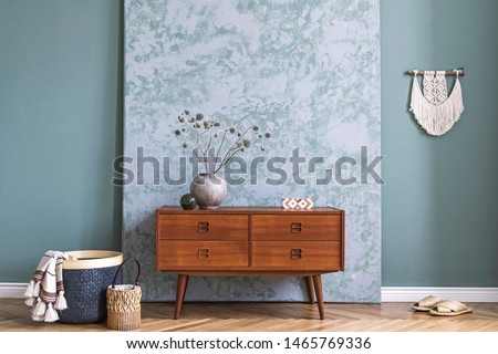 Minimalistic and boho composition of living room with wooden retro commode, vase with flowers, macrame, abstract background walls, rattan basket and elegant accessories. Modern home decor. Template.