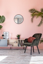 Minimalistic and luxury pastel pink home interior with green velvet design armchair, plants and mirror