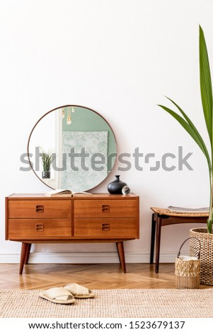 Minimalistic and stylish composition of living room with wooden commode, mirror, tropical plant, footrest and elegant personal accessories. Interior design, Home decor. template. White walls.