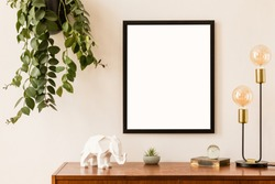 Minimalistic and stylish mock up poster frame concept with retro furnitures, hanging plant, gold table lamp and elegant accessories. White walls, home decor. Nice interior of living room. Real photo.