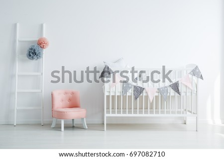 Minimalistic baby's room interior with an elegant, small, chic, pink chair, a decorated ladder, and a child's bed #697082710