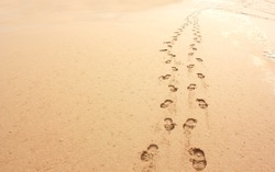 Minimalistic beach scene of two sets of foot prints in sand