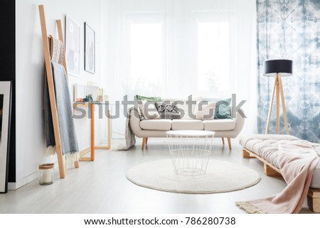 Minimalistic boho bedroom interior with a beige mattress lying on a wooden pallet and bright sofa #786280738