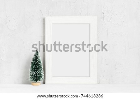 Minimalistic Christmas mock-up with white wooden frame and small tree on the table #744618286