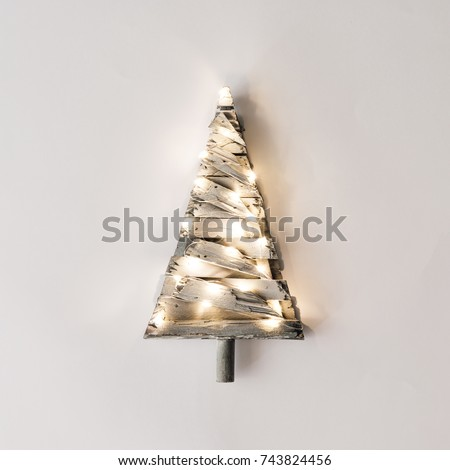 Shutterstock Minimalistic Christmas tree with lights on bright background. New Year nature minimal concept.