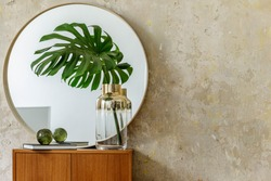 Minimalistic composition at modern retro interior with design commode, tropical leaves in vase, round mirror, copy space, book, grunge wall and elegant accessories in stylish home decor.