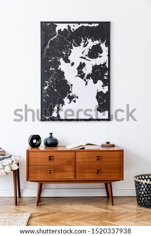 Minimalistic composition of living room with mock up poster frame, wooden retro commode, footrest, rattan basket and elegant personal accessories. Vintage home decor. Template.