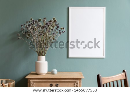 Minimalistic composition of sitting room interior with white mock up frame, wooden shelf, retro chair, rattan basket and elegant accessories. Design home decor. Template. Eucalyptus color concept.