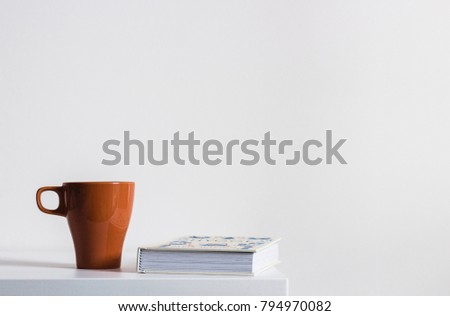 Minimalistic cosy home concept. Orange mug of tea or coffee and book on white background. White walls and white wooden table. Scandinavian interior, lazy winter day at home. #794970082