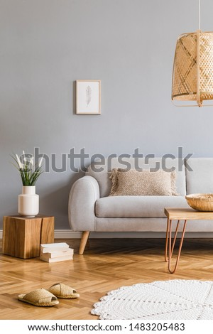Minimalistic design home interior of living room with gray sofa, wooden coffee table, photo frame, flowers, rattan lamp, basket and elegant accessories. Stylish home decor. Template. Gray walls.