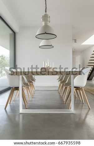 Minimalistic dining zone in open space of big modern house #667935598