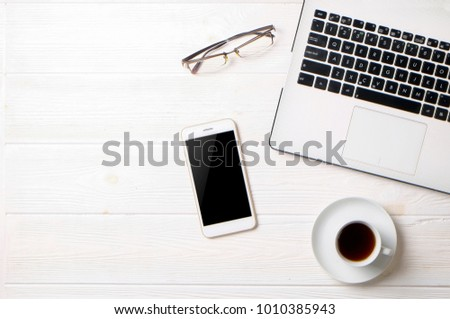 Minimalistic flat lay composition of black & white laptop computer keyboard, cell phone gadget, cup of coffee & folded glasses on textured wooden desk table background. Workspace top view, copy space #1010385943