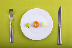 Minimalistic food composition with different types of products on white plate, knife and fork on green background. Concept of conscious nutrition.