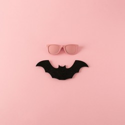 Minimalistic Halloween happy face made of pink sunglasses and black bat on pink background. Creative funny Halloween concept. Top view.