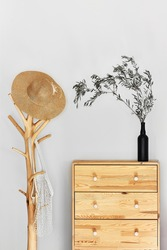 Minimalistic hallway interior with trendy wooden clothes hanger stand and commode against a gray wall.Wicker hat and mesh bag on the hanger.Copy space