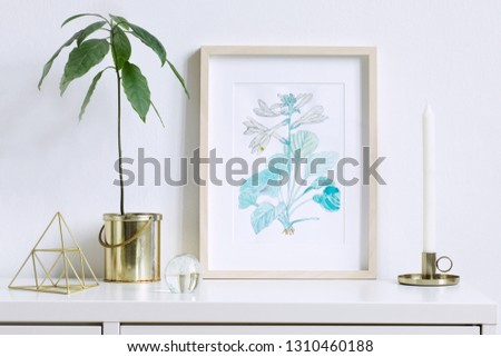 Minimalistic home interior floral poster mock up with vertical wooden photo frame, avocado plant, gold pyramid and accessories on white wall background. Concept of white shelf. #1310460188