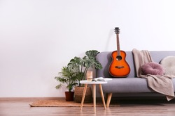 Minimalistic interior design concept. Acoustic guitar on grey textile sofa in spacious room of loft style apartment with wood textured laminated flooring. Background, copy space, close up.