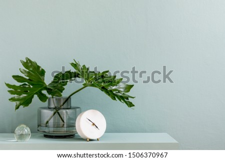 Minimalistic interior design of living room at nice apartment with stylish shelf, vase with ftropical leaf, white clock and elegant accessories. Copy space. Eucalyptus color concept. Template.