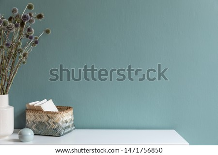 Minimalistic interior design of living room at nice apartment with stylish shelf, vase with flowers, rattan basket with books and elegant accessories. Copy space. Eucalyptus color concept. Template.