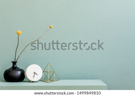 Minimalistic interior design of living room at nice apartment with stylish shelf, vase with flowers, gold pyramid, clock and elegant accessories. Copy space. Eucalyptus color concept. Template.