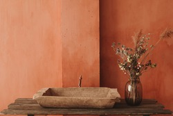 Minimalistic interior style. Dry flowers in a glass vase standing on a wooden shelf with a vintage sink at the orange wall background