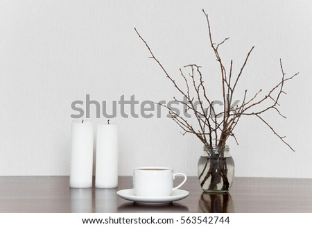 Minimalistic still life with cup, candles and branches in bottle on a wooden table. Romantic grey and white stylish interior still life